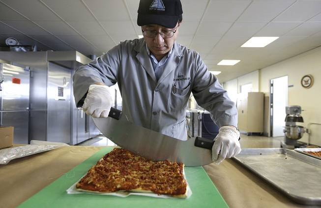 In this Thursday, Feb. 6, 2014 photo, food technologist Tom Yang cuts a prototype pizza at the U.S. Army Natick Soldier Research, Development and Engineering Center, in Natick, Mass.