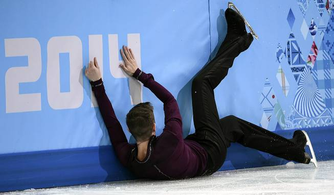 Jeremy Abbott of the United States crashes into the boards after falling during the men's short program figure skating competition at the Iceberg Skating Palace during the 2014 Winter Olympics, Thursday, Feb. 13, 2014, in Sochi, Russia.