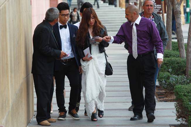 Anthony Mastrangelo, left, and Israel Reyes try to sell Tai Nguyen and Ivy Dinh on their wedding chapel services outside the Marriage Bureau at the Regional Justice Center Friday, Feb. 14, 2014.