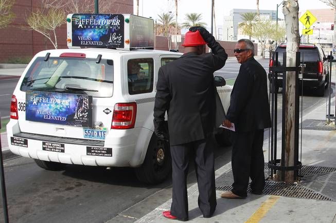 Darryl Jones, left, and Anthony Mastrangelo wait for a couple to exit a cab outside the Marriage Bureau at the Regional Justice Center to try and sell them on their wedding chapel services Friday, Feb. 14, 2014.