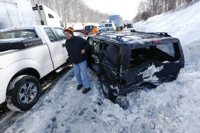 A man gets out of a SUV, one of many vehicles piled up in an accident, Friday, Feb. 14, 2014, in Bensalem, Pa. Traffic accidents involving multiple tractor trailers and dozens of cars have completely blocked one side of the Pennsylvania Turnpike outside Philadelphia and caused some injuries.