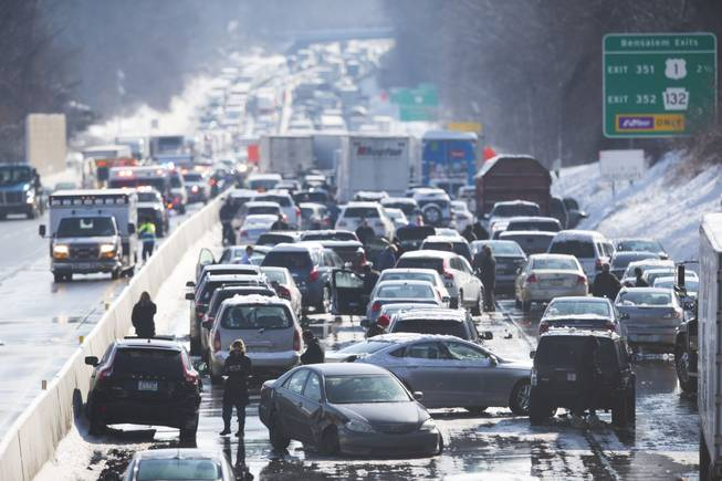 Vehicles are piled up in an accident Friday, Feb. 14, 2014, in Bensalem, Pa. Traffic accidents involving multiple tractor trailers and dozens of cars completely blocked one side of the Pennsylvania Turnpike outside Philadelphia and caused some injuries.