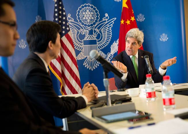 U.S. Secretary of State John Kerry, right, gestures during a discussion with Chinese bloggers on a number of issues, including internet freedom, Chinese territorial disputes with Japan, North Korea, and human rights, on Saturday, Feb. 15, 2014, in Beijing, China.