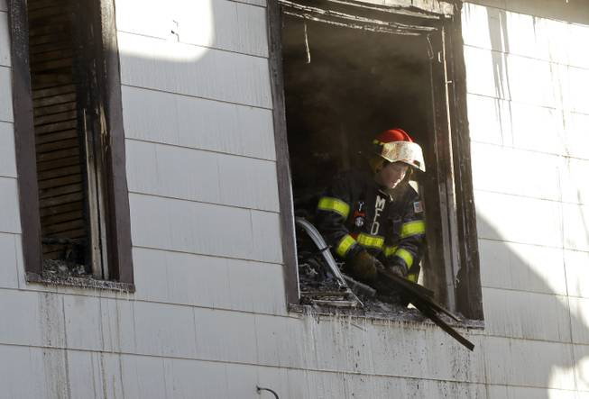 A Minneapolis firefighter throws out debris from the second floor of a North Minneapolis duplex after an early morning fire Friday, Feb. 14, 2014.