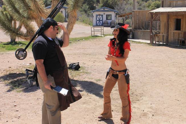 "Melody Sweets, in costume, on set at Grand Canyon Ranch in April 2013 for the filming of her video for the song, ""Shoot 'em Up."" The actor dressed as a butcher is ""Absinthe"" company manager Daniel Kells."