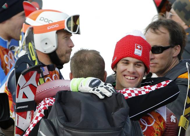 Men's supercombined gold medalist, Switzerland's Sandro Viletta, right, embraces another athlete as United States' Bode Miller, left, stands nearby in the finish area of the Alpine ski venue at the Sochi 2014 Winter Olympics, Friday, Feb. 14, 2014, in Krasnaya Polyana, Russia.