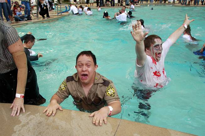 Matt Ficus, left, and Kevin Rutter react after leaping into the pool during the Fifth Annual Special Olympics Las Vegas Polar Plunge Saturday, Feb. 15, 2014 at the South Point.