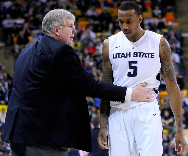 Utah State coach Stew Morrill, left, talks with Jarred Shaw, who walks off the court during an NCAA college basketball game against UNLV, Saturday, Feb. 15, 2014, in Logan, Utah.