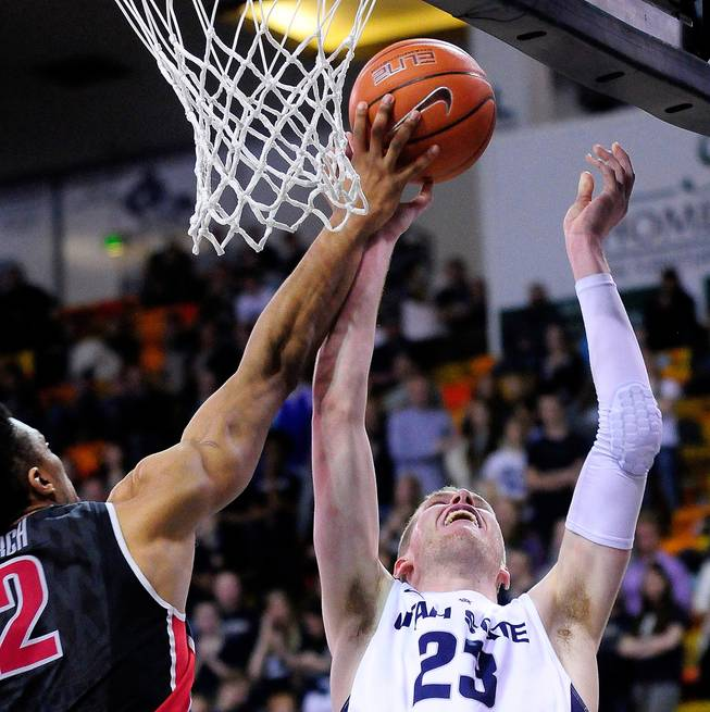UNLV's Khem Birch, left, blocks a shot by Utah State's Kyle Davis during an NCAA college basketball game on Saturday, Feb. 15, 2014, in Logan, Utah.