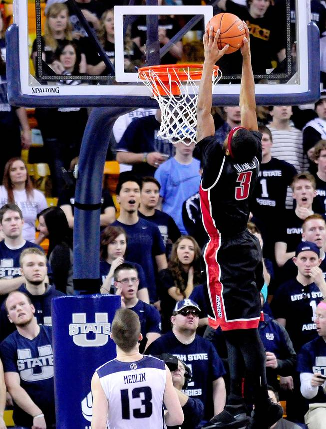 UNLV's Kevin Olekaibe (3) dunks the ball over Utah State's Preston Medlin during an NCAA college basketball game on Saturday, Feb. 15, 2014, in Logan, Utah.