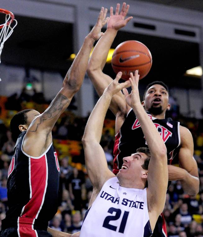 Utah State's Spencer Butterfield (21) has his shot blocked by UNLV's Bryce Dejean-Jones, left, and Khem Birch during an NCAA college basketball game on Saturday, Feb. 15, 2014, in Logan, Utah.