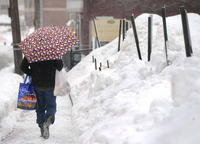 Pam Yeaple walks home after grocery shopping in York, Pa., on Saturday, Feb. 15, 2014. An inch of new snow had fallen by midday in much of eastern Pennsylvania on Saturday. Forecasters predicted 2 to 5 inches before evening.