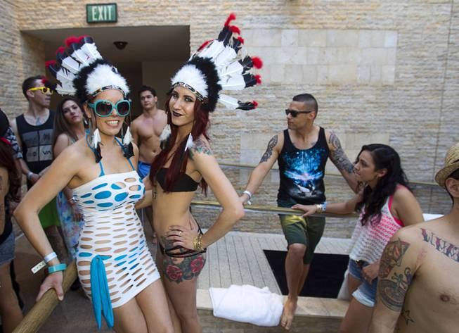 Angel Alcantar and Kylie Doughman wear Indian headdresses during the Halfway to EDC and first winter pool party at Marquee Dayclub on Sunday, Feb. 16, 2014, in the Cosmopolitan of Las Vegas.