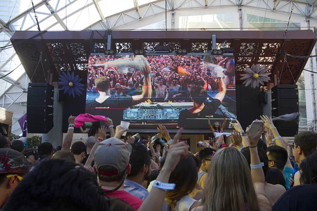 Partygoers listen to electronic dance music by Firebeatz (shown on the video screen) during the Halfway to EDC and first winter pool party at Marquee Dayclub on Sunday, Feb. 16, 2014, in the Cosmopolitan of Las Vegas.