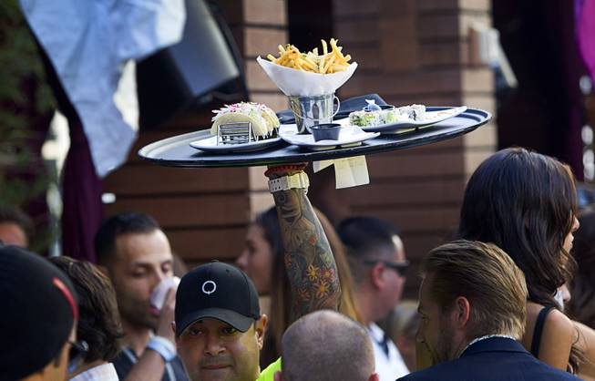 A waiter brings an order of food through the crowded bungalow area during the Halfway to EDC and first winter pool party at Marquee Dayclub on Sunday, Feb. 16, 2014, in the Cosmopolitan of Las Vegas.