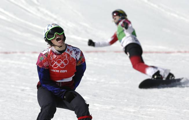 Czech Republic's Eva Samkova, left, celebrates after taking the gold medal in the women's snowboard cross final, ahead of silver medalist Dominique Maltais of Canada, right, at the Rosa Khutor Extreme Park, at the 2014 Winter Olympics on Sunday, Feb. 16, 2014, in Krasnaya Polyana, Russia.