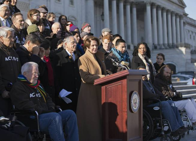 "In this Dec. 12, 2013, file photo House Minority Leader Nancy Pelosi, D-Calif., at the podium, is joined by Congressional Hispanic Caucus Chairman Rep. Ruben Hinojosa, D-Texas, to her left, as she calls for action on immigration reform on Capitol Hill in Washington with other lawmakers and activists. Democrats are planning to rely on an infrequently used and rarely successful tactic to shine an election-year spotlight on Republican opposition to raising the minimum wage and overhauling immigration laws: it's known as a ""discharge petition."" It requires the minority party to persuade some two dozen Republicans to defy their leadership."