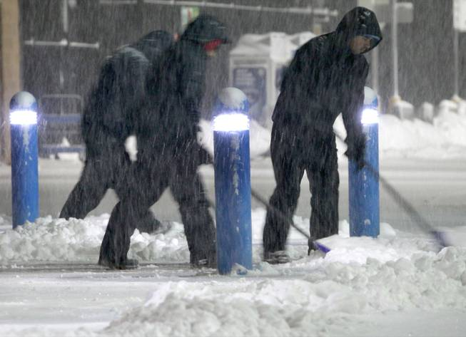 Workers clears snow from the sidewalk outside a business Saturday, Feb. 15, 2014, in the Boston suburb of Hudson, Mass. Another round of snow made its way into the Northeast on the heels of a storm that brought snow and ice to the East Coast, caused at least 25 deaths and left hundreds of thousands without power.