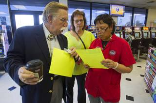 Volunteers Edward Cotton, left, and Maria Brezinski, center, talk with Rebel store manager Patty Patacsil as they hand out fliers on missing woman Jessie Foster near Jones Boulevard and Tropicana Avenue Monday, Feb. 17, 2014. Foster, a Canadian, went missing from North Las Vegas in 2006.