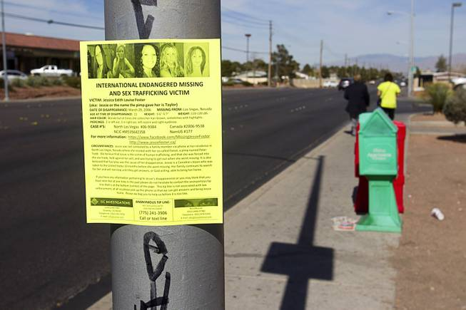 Volunteers Edward Cotton, left, and Maria Brezinski, post fliers on missing woman Jessie Foster on Jones Boulevard and Tropicana Avenue Monday, Feb. 17, 2014. Foster, a Canadian, went missing from North Las Vegas in 2006.