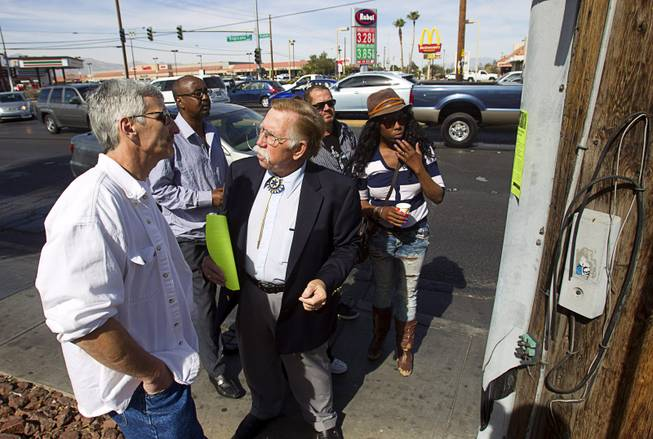Volunteer Edward Cotton, center, talks with Jeff Hoffman, left, and other passers-by as he searches for information on missing woman Jessie Foster near Jones Boulevard and Tropicana Avenue Monday, Feb. 17, 2014. Foster, a Canadian, went missing from North Las Vegas in 2006.