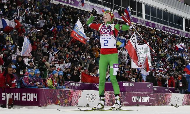 Belarus' Darya Domracheva celebrates winning the gold medal in the women's biathlon 12.5k mass-start, at the 2014 Winter Olympics, Monday, Feb. 17, 2014, in Krasnaya Polyana, Russia.
