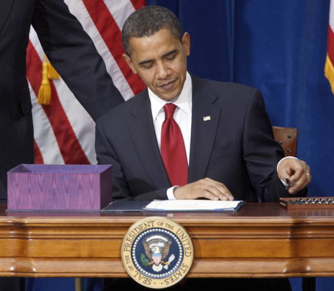 This Feb. 17, 2009, file photo shows President Barack Obama picking up the first pen to sign the economic stimulus bill during a ceremony in the Museum of Nature and Science in Denver.