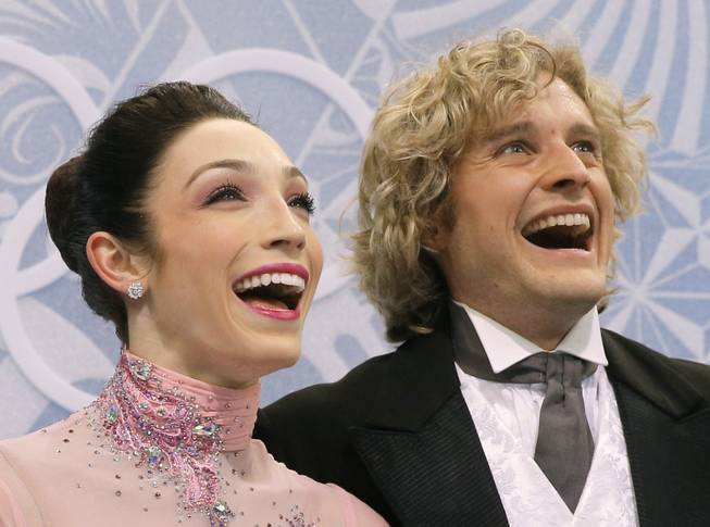 Meryl Davis and Charlie White of the United States smile as they wait in the results area after competing in the ice dance short dance figure skating competition at the Iceberg Skating Palace during the 2014 Winter Olympics, Sunday, Feb. 16, 2014, in Sochi, Russia.