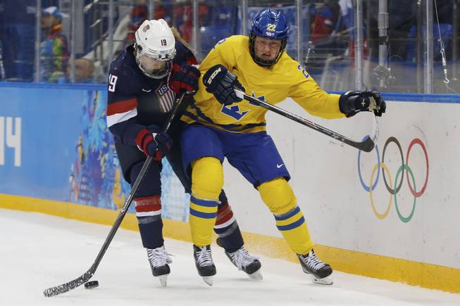 Gigi Marvin of the United States and Emma Eliasson of Sweden battle fro control of the puck during the second period of the 2014 Winter Olympics women's semifinal ice hockey game at Shayba Arena Monday, Feb. 17, 2014, in Sochi, Russia.