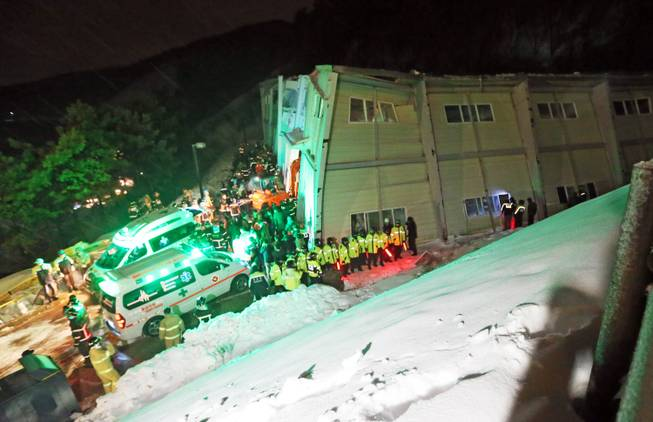 Rescue workers search for survivors from a collapsed resort building in Gyeongju, South Korea, Monday, Feb. 17, 2014. South Korean police and news reports say that dozens of university students are feared trapped after a building's roof collapsed because of recent heavy snowfall.