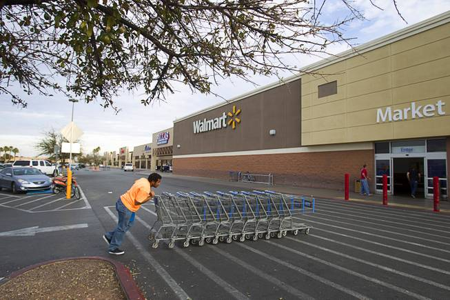 An employee gathers carts at the Walmart Supercenter at 3075 E Tropicana Ave. Tuesday, Feb. 18, 2014. The shopping center had been decline during the recession but is now recovering and adding tenants.