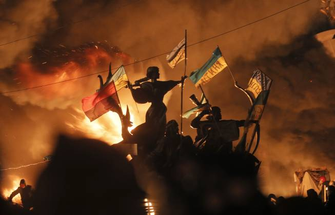 Monuments to Kiev's founders burn as anti-government protesters clash with riot police in Kiev's Independence Square, the epicenter of the country's current unrest,  Kiev, Ukraine, Tuesday, Feb. 18, 2014.