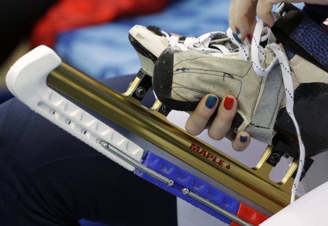 Tatiana Borodulina of Russia laces up before the start of the short track speedskating competition at the Iceberg Skating Palace during the 2014 Winter Olympics, Tuesday, Feb. 18, 2014, in Sochi, Russia.
