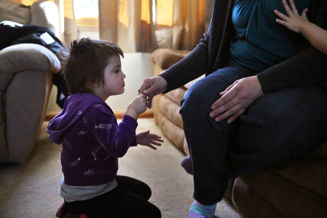 In this Feb. 7, 2014 photo, Elizabeth Burger, 4, holds her mother's hand at home in Colorado Springs, Colo. Elizabeth suffers from severe epilepsy and is receiving experimental treatment with a special strain of medical marijuana, which she takes orally as drops of oil.