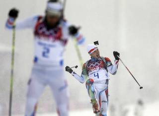 Czech Republic's Ondrej Moravec, right, celebrates winning the bronze medal next to silver medalist France's Martin Fourcade, during the men's biathlon 15k mass-start, at the 2014 Winter Olympics, Tuesday, Feb. 18, 2014, in Krasnaya Polyana, Russia.