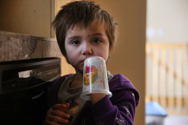 In this Feb. 7, 2014 photo, Elizabeth Burger, 4, plays with a decorative plastic cup at home in Colorado Springs, Colo. Elizabeth suffers from severe epilepsy and is receiving experimental treatment with a special strain of medical marijuana, which she takes orally as drops of oil.