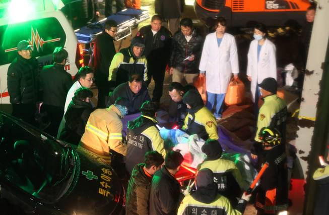 Rescue workers carry a victim, medical condition unknown, from a collapsed resort building in Gyeongju, South Korea, Monday, Feb. 17, 2014.  South Korean police and news reports say that dozens of university students are feared trapped after a buildingis roof collapsed because of recent heavy snowfall.