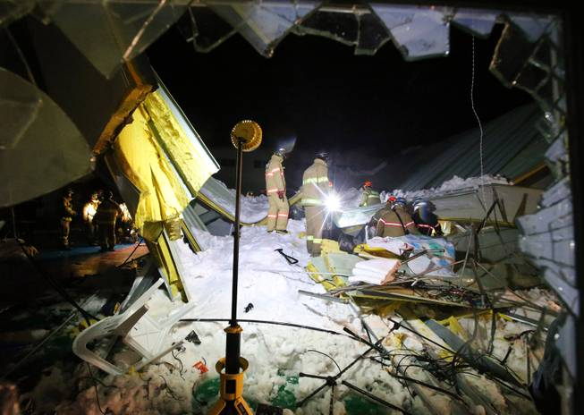 Rescue workers search for survivors from a collapsed resort building in Gyeongju, South Korea, Monday, Feb. 17, 2014.  Four university students died and about 10 were feared trapped after the roof of a building collapsed in a southeastern city during a welcoming ceremony for freshmen, South Korean officials said Tuesday.