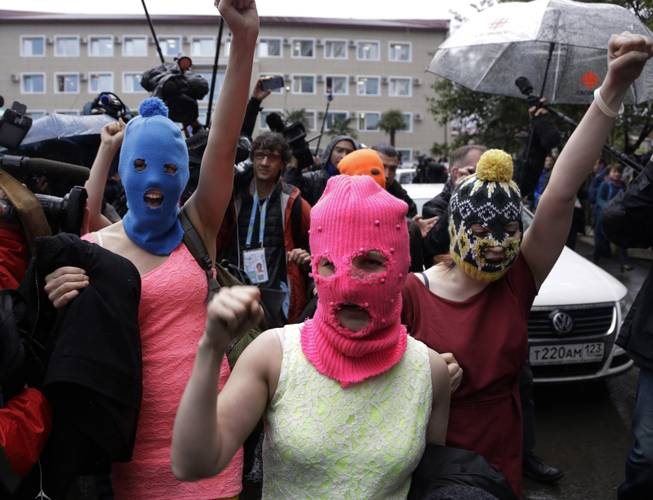 Russian punk group Pussy Riot members Nadezhda Tolokonnikova, in the blue balaclava, and Maria Alekhina, in the pink balaclava, make their way through a crowd after they were released from a police station, Tuesday, Feb. 18, 2014, in Adler, Russia.