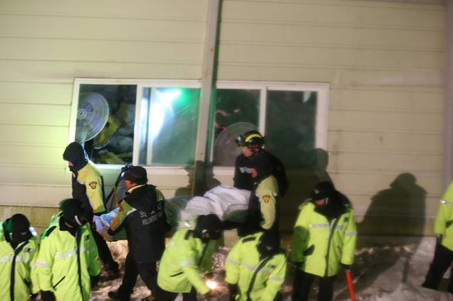Rescue workers carry a body from a collapsed building in Gyeongju, South Korea, Monday, Feb. 17, 2014. South Korean police and news reports say that dozens of university students are feared trapped after a buildingis roof collapsed because of recent heavy snowfall.