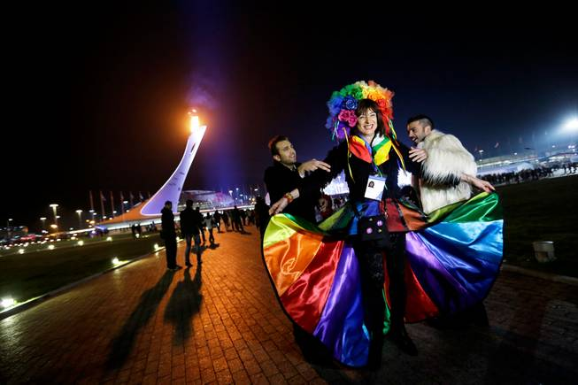Vladimir Luxuria, center, a former Communist lawmaker in the Italian parliament and prominent crusader for transgender rights, is led away by friends to attend a women's ice hockey match after posing for photos on the Olympic Plaza at the 2014 Winter Olympics, Monday, Feb. 17, 2014, in Sochi, Russia. Luxuria was soon after detained by police upon entering the Shayba Arena.