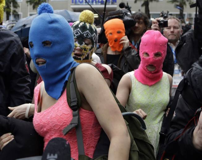 Russian punk group Pussy Riot members Nadezhda Tolokonnikova, in the blue balaclava, and Maria Alekhina, in the pink balaclava, make their way through a crowd after they were released from a police station, Tuesday, Feb. 18, 2014, in Adler, Russia. No charges were filed against Tolokonnikova and Alekhina along with the three others who were detained.