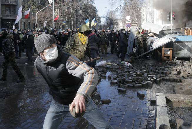 Anti-government protesters lob stones during clashes with riot police outside Ukraine's parliament in Kiev, Ukraine, Tuesday, Feb. 18, 2014. Some thousands of angry anti-government protesters clashed with police in a new eruption of violence Tuesday.