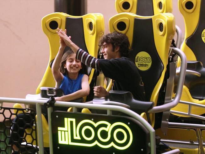 Benjamin de los Santos, left, and Chris McKenna high five after being the first to ride the El Loco roller coaster at Circus Circus Tuesday, Feb. 18, 2014.