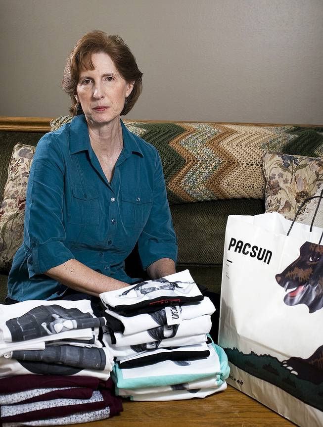Judy Cox sits for a portrait next to a stack of T-shirts with what she believes are pornographic designs Monday, Feb. 17, 2014, in Orem, Utah.