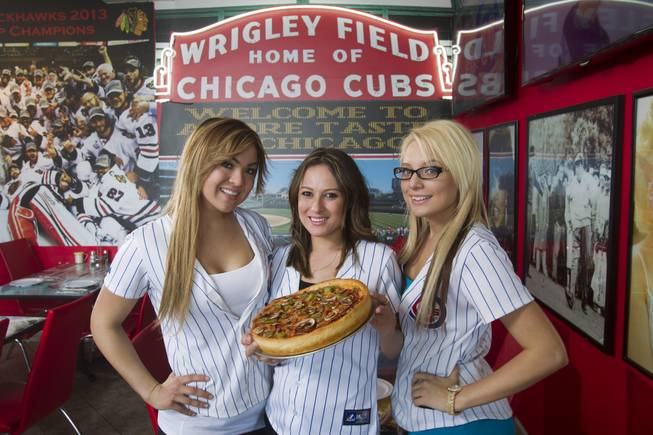 Servers, from left, Tiffany Shapouri, Susie Barajas, and Amanda Hewitt pose with a medium-size, three-topping, deep-dish pizza at Amore Taste of Chicago, 3945 S. Durango Dr., Wednesday, Feb. 19, 2014. This pizza ($20.50) has pepperoni, mushrooms and green peppers over fresh crushed tomatoes.