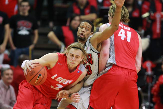 UNLV guard Bryce Dejan Jones is screened by New Mexico forward Cameron Bairstow as guard Hugh Greenwood moves to the basket during the first half of their Mountain West Conference game Wednesday, Feb. 19, 2014 at the Thomas & Mack Center.