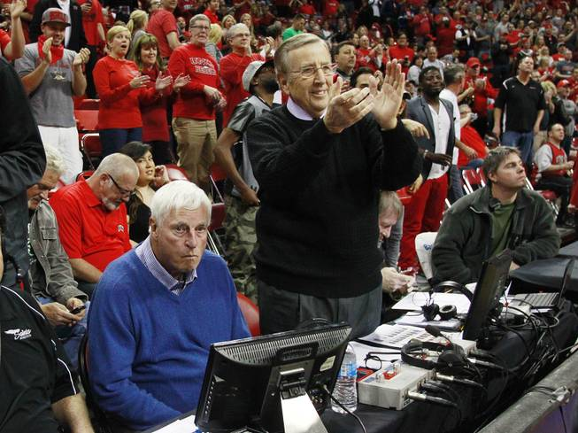 As former UNLV head coach Jerry Tarkanian makes his way across the court to his seat, ESPN broadcaster Brent Musberger joins others at the Thomas & Mack Center in a standing ovation while fellow broadcaster and former Indiana coach Bobby Knight remains seated before the Rebels game against New Mexico Wednesday, Feb. 19, 2014.
