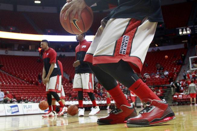 UNLV guard Kevin Olekaibe sports shoes featuring lights in the heels and Hey Reb on the tongue while the Rebels warm up for their game against New Mexico Wednesday, Feb. 19, 2014 at the Thomas & Mack Center.