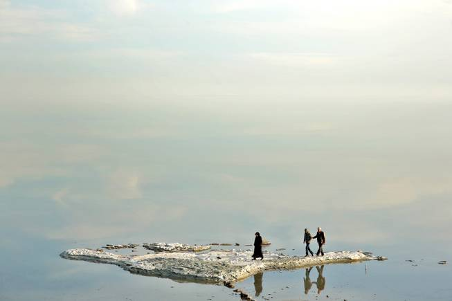 In this  Saturday, Feb. 15, 2014 photo, visitors walk on salt-covered rocks that were once deep underwater at Lake Oroumieh Lake, northwestern Iran.